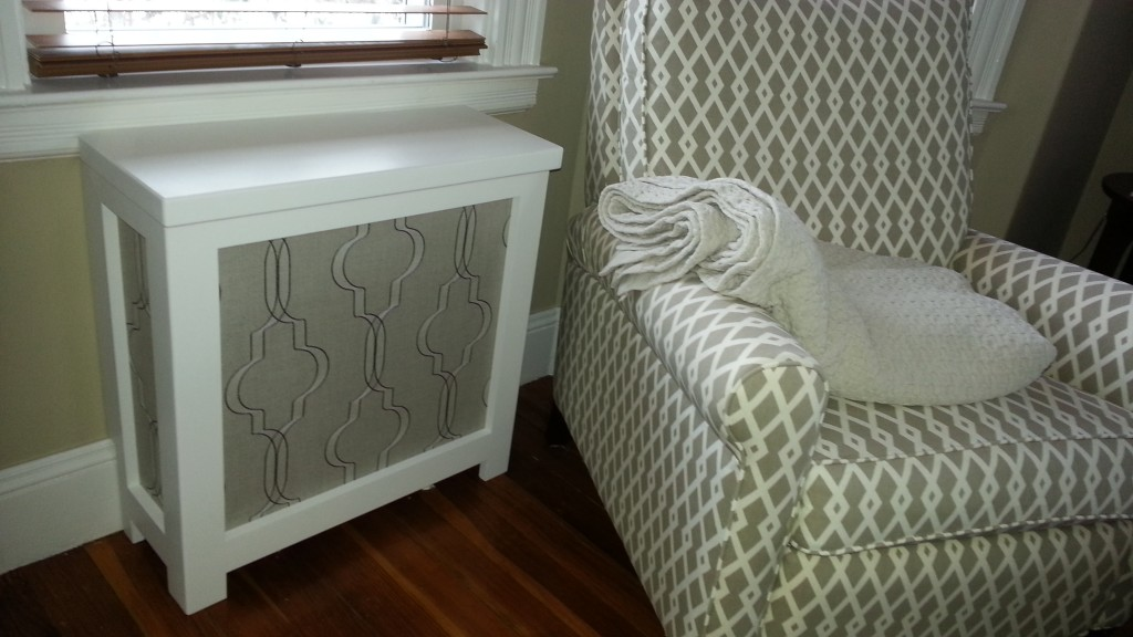White frame radiator cover next to a living room chair